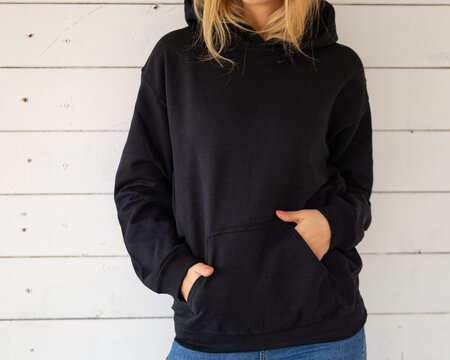 Sweatshirt hoodie mockup. Unrecognizable woman poses in a black sweatshirt against the background of white boards, facing the camera.
