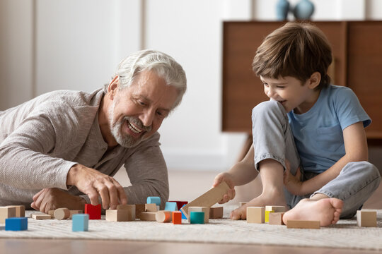 Loving elderly Caucasian grandfather have fun playing with little 6s boy child building with blocks. Happy caring mature grandparent engaged in funny game activity with small grandson at home.