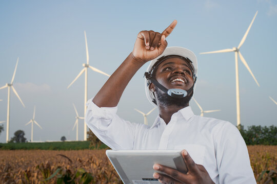 African engineer wearing white hard hat standing with digital tablet against wind turbine