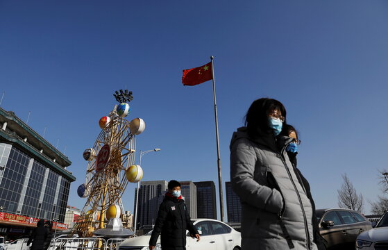 People wearing face masks walk past a Chinese flag, following new cases of the coronavirus disease (COVID-19) in the country, in Beijing