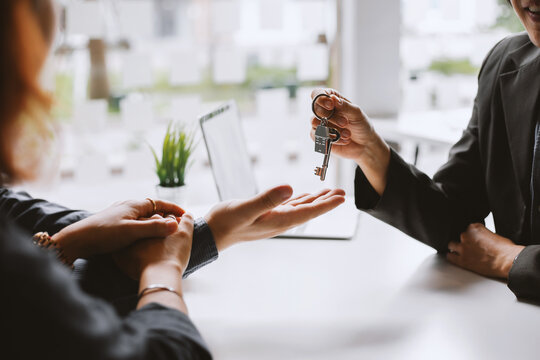 Real estate agent giving house key to the client after signing the real estate contract. Home and real estate trading concept.