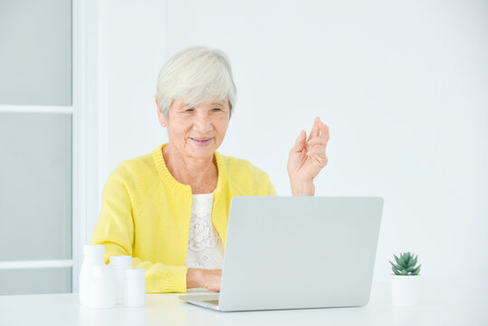 Senior woman sitting in front of laptop computer making video call chat with doctor. Telemedicine concept.