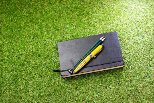 Caneta tinteiro e lápis em cima de caderno em couro