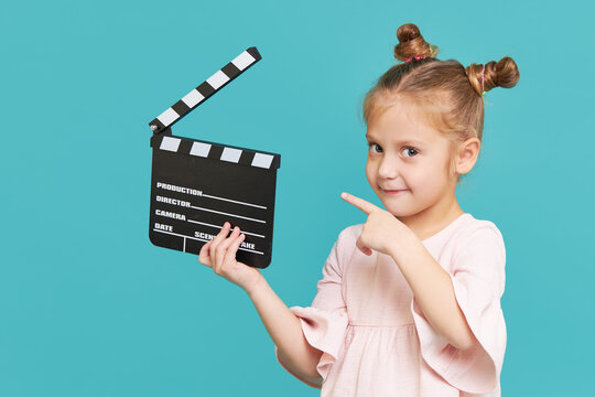 Funny smiling child girl hold film making clapperboard isolated on blue background. Little clipmaker, acting training. Funny face. Copy space for text..