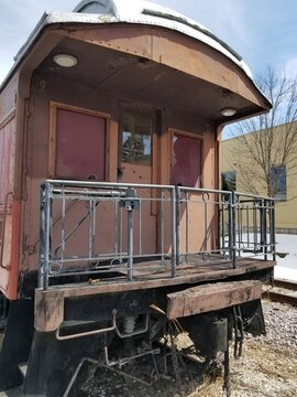 The Back View Of A Vintage Caboose Sitting In A Train Yard.