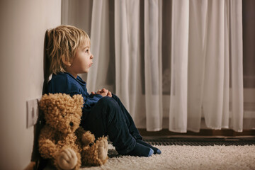 Sad little toddler child, blond boy, sitting in corner with teddy bear, punished