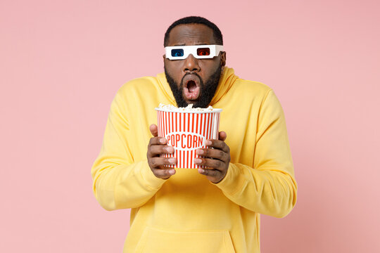 Shocked worried young african american man 20s in yellow streetwear hoodie 3d glasses watching movie film hold bucket of popcorn keeping mouth open isolated on pink color background studio portrait.