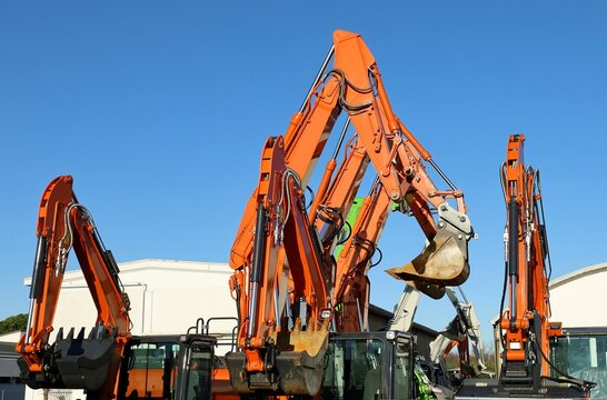 Booms and buckets of orange excavators  raising up in the air outside a dealer