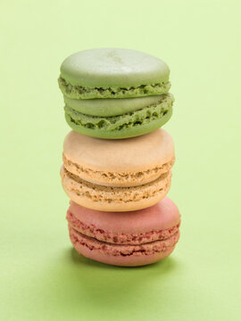 French macarons pastry variety stacked on pastel green background