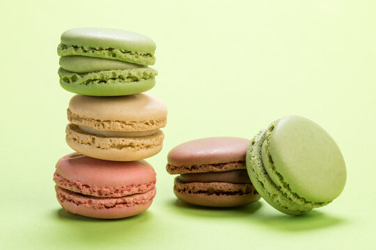Variety of pastel colored french macarons pastry on light green background