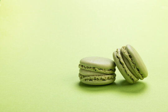 Pistachio flavor macaron cookies on pastel green colored background