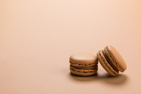 Coffee flavor macaron cookies on pastel brown colored background