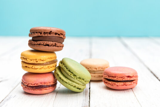 French macarons pastry variety with vanilla, coffee and chocolate flavours on rustic wooden surface, blue background