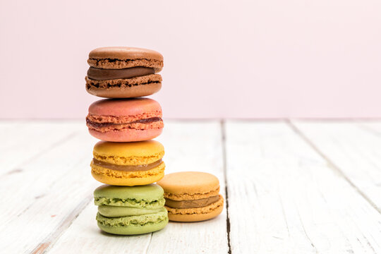 Stack of colorful french macarons pastry on rustic white table