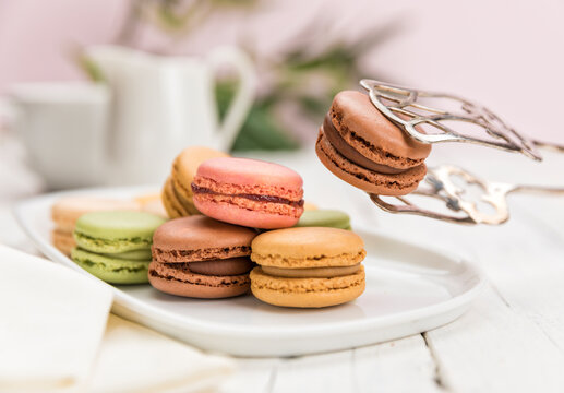 Variety of macarons on a plate, a chocolate cookie held  with pastry tongs, shallow depth of field.