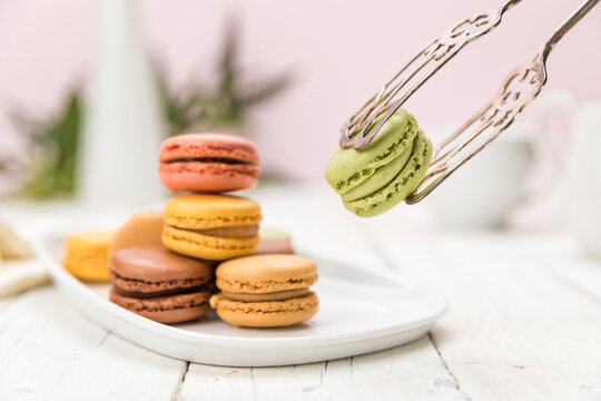 French macarons pastry on coffee table, one held up with pastry tongs