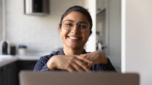 Close up view of smiling 20s young Indian woman in glasses working on laptop at home office. Happy millennial ethnic female wear spectacles for eyesight correction using computer at workplace.