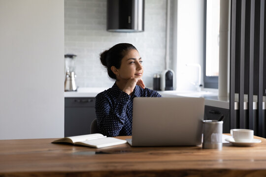 Dreamy young Indian woman sit at desk work on laptop look in distance thinking or visualizing. Happy thoughtful millennial ethnic female distracted from computer make plan or imagine success.