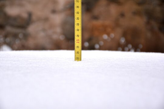 Yellow tape measure measuring snow cover after the storm. Filomena snow storm in La Rioja, Spain, January 2021.