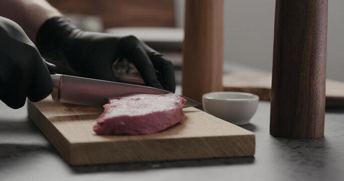 man cut raw beef steak on oak board