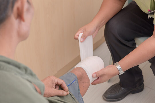Low Section Of Doctor Wrapping Bandage On Leg In Hospital