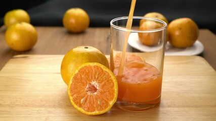 Fototapete - Pour orange juice into a glass with orange fruit whole and halves on wooden cutting board.