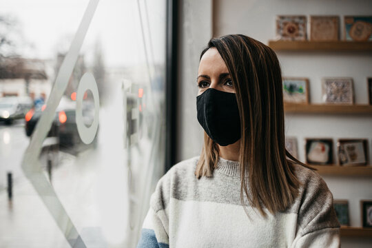 Young female artist standing in front of workshop window and looking outside. She is wearing protective face mask. Art in Coronavirus lockdown time concept.