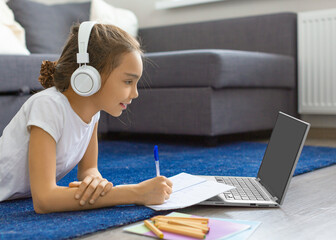 Teenager girl doing her homework online in front of a laptop monitor lying on the floor at home.