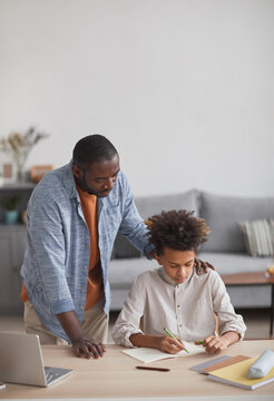 Vertical portrait of proud African-American father helping son doing homework at desk in minimal home interior, copy space