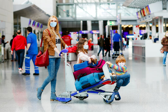 Two little kids, boy and girl and mother in medical mask at airport. Children, family travel by plane during corona virus pandemic lockdown. People in mask as preventive measure and covid protection
