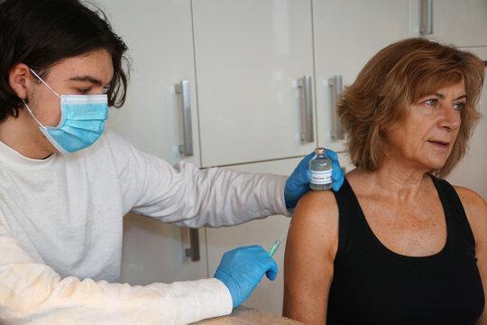 Ein junger Arzt impft eine ältere Patientin gegen Corona