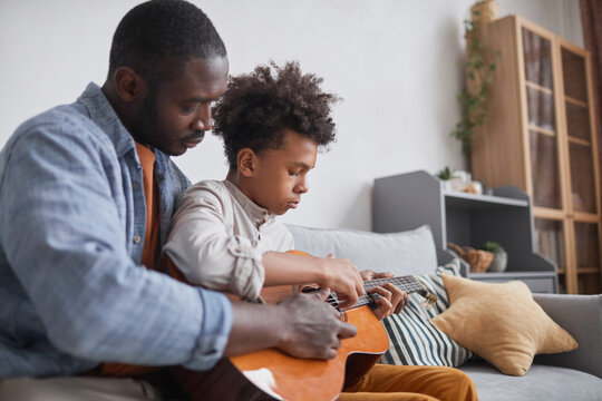 Modern African American man spending free time with his teen son at home teaching him how to play guitar
