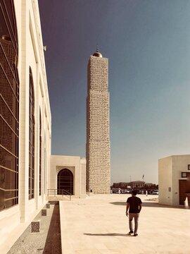 Rear View Of Man Walking In Building Against Sky