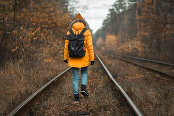 Girl tourist travels through the autumn forest along the railway. Fotobehang