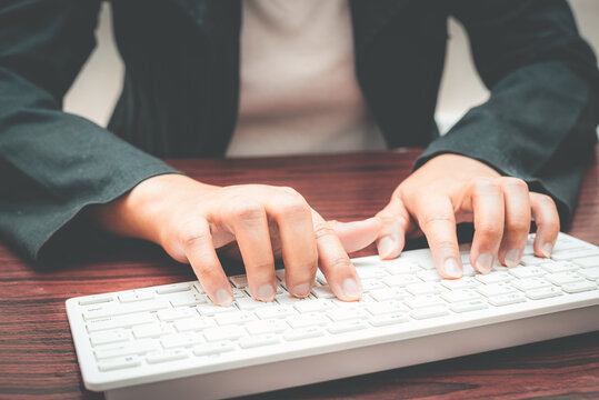 close-up of business woman hand typing and using laptop keyboard for searching with technology networking on working and job on desk at work place or work at home.