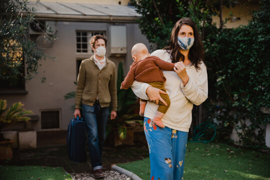 Young family with small child leaving their holiday accommodation - People wearing protective face masks against Covid-19 infections, Coronavirus, man carries suitcase while woman holds her child