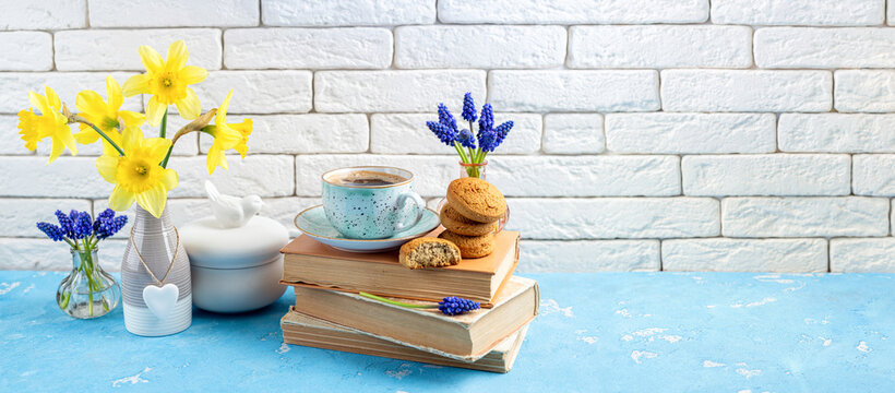 Bouquets of spring flowers, coffee cup, books, cookies on blue table over white brick background. Reading and breakfast. Concept spring, hygge and cozy home interior. Copy space