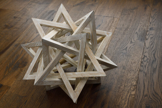Five interlocked wood pyramids forming a spiked ball on dark wood floor