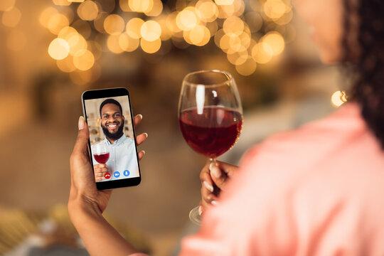 Black couple having online date on phone, drinking wine