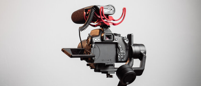 DSLR Camera on Gimbal Stabilizer With Red Shotgun Microphone on White Background