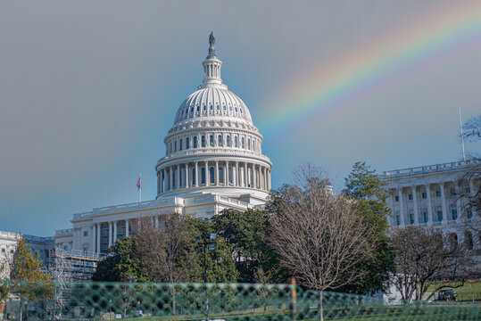 Rainbow over The United States Capitol Building, preparing construction for inauguration next to the fence on blue sky background.