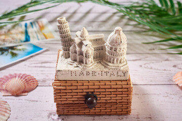 Italian souvenir from the tower of Pisa with wooden gift box on the background of the plane toy, seashells, palm leaves. Wooden background, close-up, macro. Fototapete