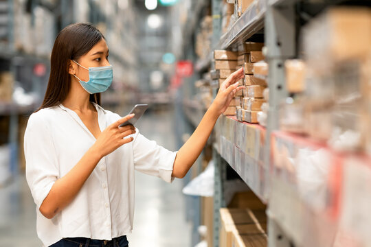 stock taking. beautiful young woman worker of furniture store with surgical mask in covid-19 situation.