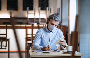 Frustrated owner sitting at table in closed cafe, small business lockdown due to coronavirus.
