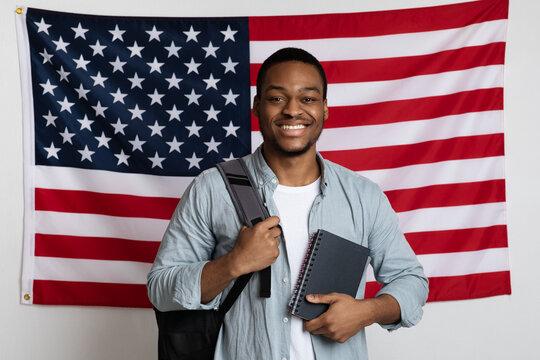 Smiling black man student standing over american flag