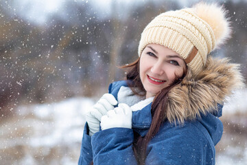 Woman in jacket smiling on the background of winter landscape. Wall mural