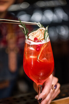 red cocktail in glass with orange peel and rosemary