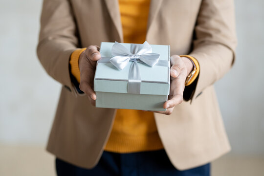 Hands of young elegant businessman passing you gift in blue box with bow