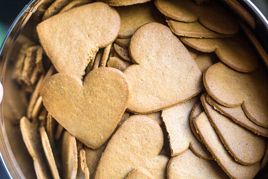 Top view to heart shaped ginger bread biscuits. Background or wallpaper in love topic. Saint Valentines sweet hearts. Bakery for tea. Many shaped gingerbreads. Close up with copy space.
