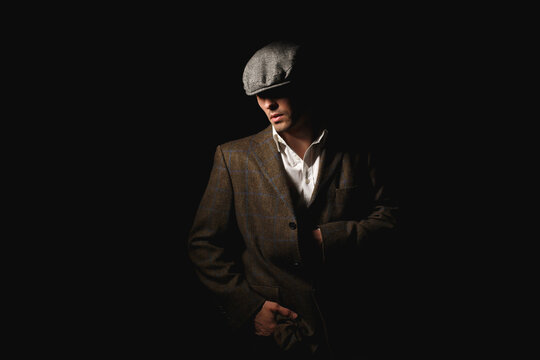 A man in a classic jacket and cap.